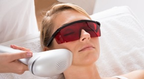 Woman Undergoing Laser Treatment At Salon