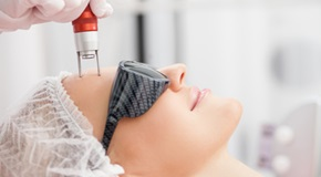 Cheerful skillful cosmetologist is treating female face